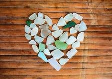 Cuore di vetro del ciottolo della spiaggia su fondo di legno Zuccheri il mosaico di vetro per il giorno del ` s del biglietto di  Immagini Stock