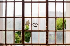 Cuore dipinto sulle finestre rotte Fotografie Stock