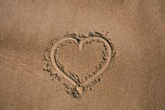Cuore dissipato nella sabbia Fondo della spiaggia con il disegno del cuore Simbolo di amore di forma del cuore come fondo Fotografia Stock Libera da Diritti