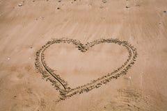 Cuore dissipato nella sabbia Fondo della spiaggia con il disegno del cuore Simbolo di amore di forma del cuore come fondo Immagini Stock