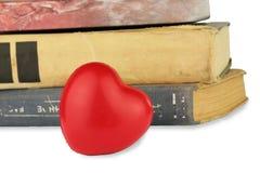 Cuore e pila rossi di vecchi libri sui precedenti bianchi Fotografia Stock