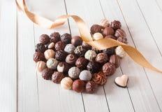 Cuore fatto con i tartufi di cioccolato con un nastro Fotografia Stock