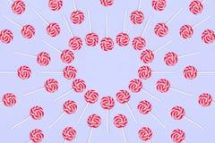 Cuore fatto dalle caramelle rosse del lollypop su fondo blu, spazio della copia Cartolina d'auguri di giorno del `s del biglietto fotografie stock libere da diritti