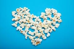 Cuore fatto di popcorn delizioso su un fondo blu immagine stock libera da diritti