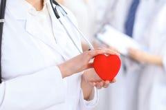 Cuore femminile della tenuta di medico in sue mani Medico e paziente che si siedono nei precedenti Cardiologia nella medicina Immagine Stock