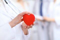 Cuore femminile della tenuta di medico in sue mani Medico e paziente che si siedono nei precedenti Cardiologia nella medicina Immagini Stock