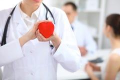 Cuore femminile della tenuta di medico in sue mani Medico e paziente che si siedono nei precedenti Cardiologia nella medicina Immagine Stock Libera da Diritti