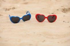 Cuore a forma di degli occhiali da sole variopinti sulla sabbia Immagini Stock Libere da Diritti