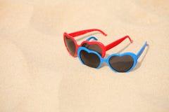 Cuore a forma di degli occhiali da sole variopinti sulla sabbia Fotografia Stock