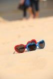 Cuore a forma di degli occhiali da sole variopinti sulla sabbia Fotografie Stock
