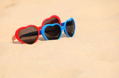 Cuore a forma di degli occhiali da sole variopinti sulla sabbia Immagine Stock Libera da Diritti