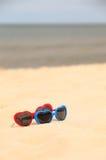 Cuore a forma di degli occhiali da sole variopinti sulla sabbia Immagini Stock