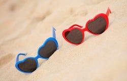 Cuore a forma di degli occhiali da sole variopinti sulla sabbia Immagine Stock