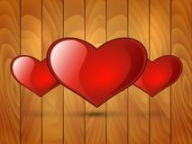Cuore lucido rosso tre su un fondo di legno Immagini Stock Libere da Diritti