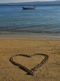 Cuore nella sabbia, barca in mare Fotografia Stock