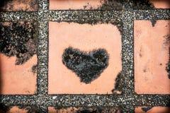 Cuore nero sul fondo concreto del pavimento Immagini Stock