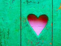 Cuore pastello rosa sulla parete rustica di legno verde Fotografie Stock