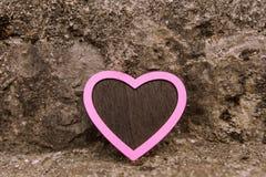 Cuore rosa d'annata davanti ad un fondo pietroso Fotografie Stock