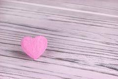 Cuore rosa di feltro su un fondo di legno grigio Giorno del biglietto di S Cartolina d'auguri Nozze, Immagini Stock