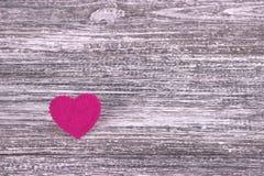 Cuore rosa di feltro su un fondo di legno grigio Giorno del biglietto di S Cartolina d'auguri Nozze, Fotografia Stock
