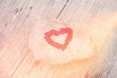 Cuore rosa dipinto con rossetto sul pezzo di pietra su fondo del bordo di legno fotografia stock