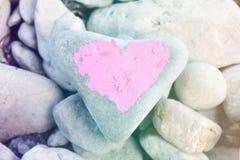 Cuore rosa dipinto con rossetto sul pezzo di pietra su fondo di molte piccole pietre fotografia stock libera da diritti