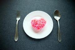 Cuore rosa lanuginoso del filo su cuore su un piatto rotondo bianco con la a immagini stock