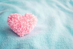 Cuore rosa lanuginoso del filo sul fondo accogliente molle blu del tessuto Ha immagini stock libere da diritti