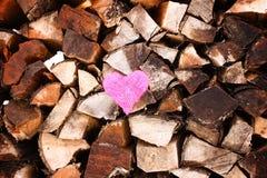 Cuore rosa sulla pila della legna da ardere Fotografia Stock