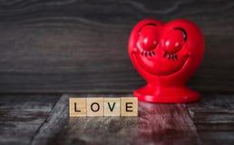 Cuore rosso ceramico con gli occhi chiusi e l'amore di parola, allineato con Fotografie Stock