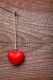 Cuore rosso che appende prima del bordo di legno Immagini Stock