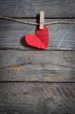 Cuore rosso che appende sulla corda da bucato Sul vecchio tema di giorno di legno background Immagine Stock