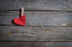 Cuore rosso che appende sulla corda da bucato Sul vecchio tema di giorno di legno background Fotografia Stock