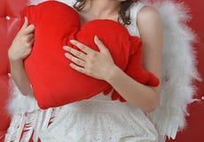 Cuore rosso che tiene la mano dell'angelo che innesta su un fondo rosso fotografie stock libere da diritti