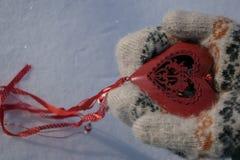 Cuore rosso con i cupidi nelle mani Fotografia Stock