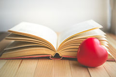 cuore rosso davanti al libro aperto con lo spazio della copia nell'umore di rilassamento Fotografia Stock Libera da Diritti