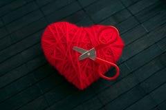 Cuore rosso del filo con le forbici attaccate rosse su backgr di legno nero fotografie stock libere da diritti