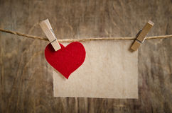 Cuore rosso del tessuto con il foglio di carta che appende sulla corda da bucato Fotografia Stock Libera da Diritti