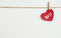 Cuore rosso del tessuto con la parola 2017 che appende sulla corda da bucato Fotografie Stock