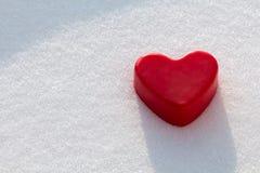 Cuore rosso della cera nella neve Immagini Stock