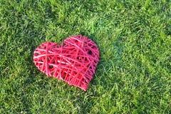 Cuore rosso della paglia sull'erba Giorno del `s del biglietto di S Fotografie Stock