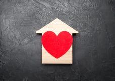 Cuore rosso dentro una casa di legno su un fondo concreto grigio Il concetto di un nido di amore, la ricerca di nuovo alloggio ac Immagini Stock Libere da Diritti