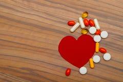 Cuore rosso e molte droghe luminose delle pillole su fondo di legno fotografia stock libera da diritti
