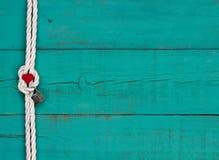 Cuore rosso e serratura che appendono sul confine bianco della corda contro il fondo blu Immagine Stock