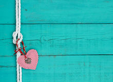 Cuore rosso e serratura che appendono sul nodo della corda contro il fondo di legno blu dell'alzavola antica Fotografie Stock Libere da Diritti