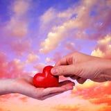 Cuore rosso in mani dell'uomo e della donna Fotografia Stock
