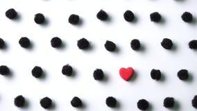 Cuore rosso nel pois nero dei poms del pom su fondo bianco immagini stock