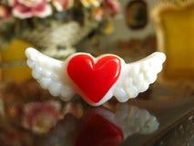 Cuore rosso pienamente colorato con le ali sulla tavola elegante immagine stock libera da diritti