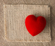 Cuore rosso su tela da imballaggio, fondo della tela di sacco Rosa rossa Immagine Stock