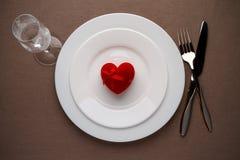 Cuore rosso su un piatto per la data romantica il giorno dei biglietti di S. Valentino Immagine Stock